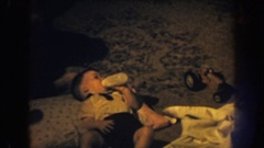1959: a set of male twins dressed up at home with mom laying down with a bottle. Stock Footage