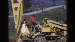 1958: construction vehicle driver operates backhoe on an open, rural field Stock Footage