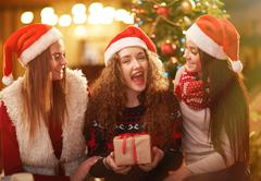 Ecstatic teenager with gift-box and her two smiling friends Stock Photos