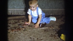 1959: a blond haired toddler crawling around on the carpet then standing and Stock Footage