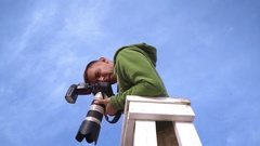 Photographer takes picture from watchtower. Photographer on sky background Stock Footage