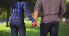 Rear view of young black couple holding hands in public park  Stock Footage