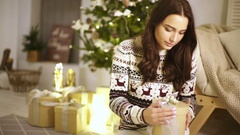 Young beautiful lady sitting on a floor and opening Christmas gifts made by her Stock Footage