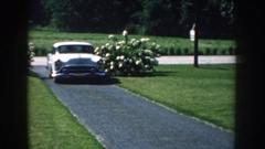 1959: plymouth driving up a narrow driveway sandwiched between green manicured Stock Footage