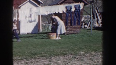 1959: woman putting laundry out to dry on a line with a child NEBRASKA Stock Footage