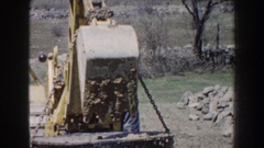 1959: a worker lifts an underground tank from the ground using a backhoe Stock Footage