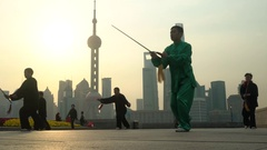 Group exercising with Tai Chi on The Bund, Shanghai, China Arkistovideo