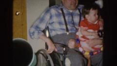 1955: disabled man holds happy bouncy child NEBRASKA Stock Footage