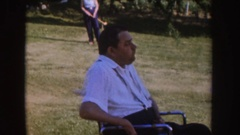 1955: man in wheelchair watching kids playing with toy tractor and croquet Stock Footage