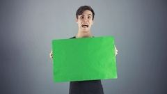 Scared Young man in black shirt holding green key sheet poster gray background Stock Footage