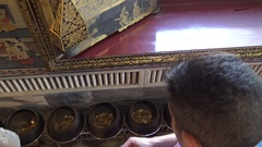 4K Visitors drop coins in bronze bowls at Wat Pho Temple Reclining Buddha-Dan Stock Footage