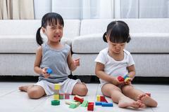 Asian Chinese little sisters struggle for blocks Kuvituskuvat