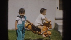1952: two small kids are playing in toy horse outside the house CALIFORNIA Stock Footage