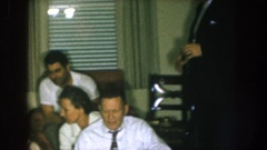 1957: a standing man in a suit places his glass down near four seated people in Stock Footage