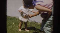 1952: mother adjusting toddler's diaper outside. CALIFORNIA Stock Footage