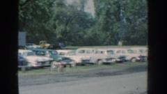 1959: row of cars fill a parking lot between trucks, trees and building for Stock Footage