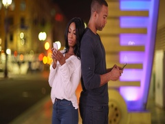 Couple standing back to back texting on cell phones Stock Footage
