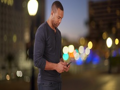 Couple texting each other and meeting on bridge overlooking city lights Stock Footage