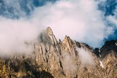 Clouds fly low over the rocks. The varied mountain landscape in Stock Photos