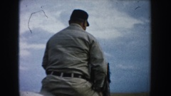 1953: man in khaki outfit and hat rides a horse in circles through a field with Stock Footage
