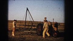 1953: three men with a tractor out in a field with an apparatus SOUTH DAKOTA Stock Footage