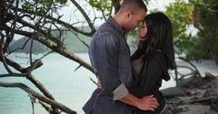 Young black couple kissing each other in secluded spot by the ocean Stock Footage