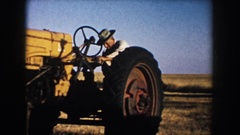 1953: man attempting to ride a yellow tractor in a barren field on a blue-sky Stock Footage