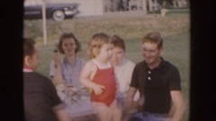1955: little girl in red leotard standing on picnic bench surrounded by adults Stock Footage