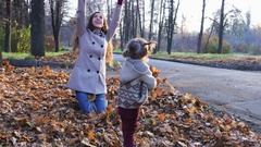 Mother with baby playing leaves outdoor. Autumn forest, park Stock Footage