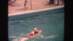 1962: small dog riding in a miniature motorboat in a pool and pretending to Stock Footage