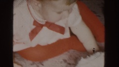 1955: a baby dressed in red sitting in front of a white frosted cake NEBRASKA Stock Footage