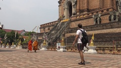 4K Buddhist monks and visitors walking around at temple Wat Chedi Luang -Dan Stock Footage