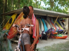 Couple sitting on bike kissing each other in front of kayak rental hut Stock Footage