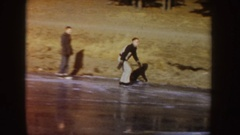 1955: man ice skating and performing tricks on a frozen lake with friends IDAHO Stock Footage