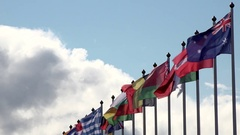 Various world flags flying on flagpoles on a background of the sky and clouds Stock Footage