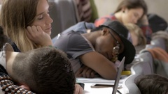 Many multi-ethnic classmates sleeping in a boring lecture Stock Footage