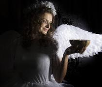 Portrait of angel and devil womans on a dark background, behind transparent Stock Photos
