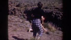 1957: two women in a desert/scrub landscape, one of them is kneeling and looking Stock Footage
