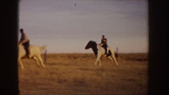 1955: two horsemen having a race in a field, wherein the white horse is on the Stock Footage