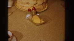 1955: cake being placed on a kitchen table with people sitting at table and Stock Footage