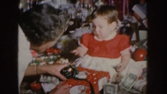 1955: mother assisting baby to unwrap a christmas present with money and objects Stock Footage
