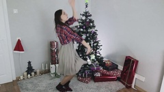 Young girl in a gray dress is dancing near the Christmas tree.  Stock Footage
