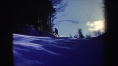1962: a man skis down a snowy slope appearing to hit two men standing in his Stock Footage