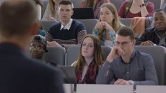 Male student actively participating in lecture and asking the professor Stock Footage