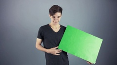 Yawning Young man in black shirt holding green key sheet poster gray background Stock Footage