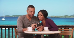 Happy Black couple on honeymoon sitting at restaurant with ocean view drinking Stock Footage