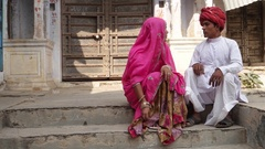 Indian couple in front of old Rajasthani architecture sitting and chatting  Stock Footage