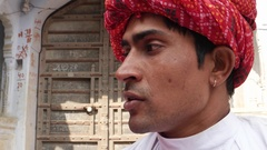 Pan close up from a handsome man with red turban to a pretty lady in pink sari t Stock Footage