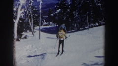 1962: two people skiing on the snow slowly and a red winch rope car VERMONT Stock Footage