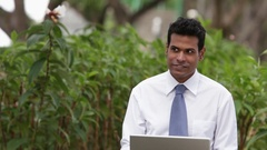 MS Businessman using laptop, punching air with clenched fist sitting outdoors Stock Footage